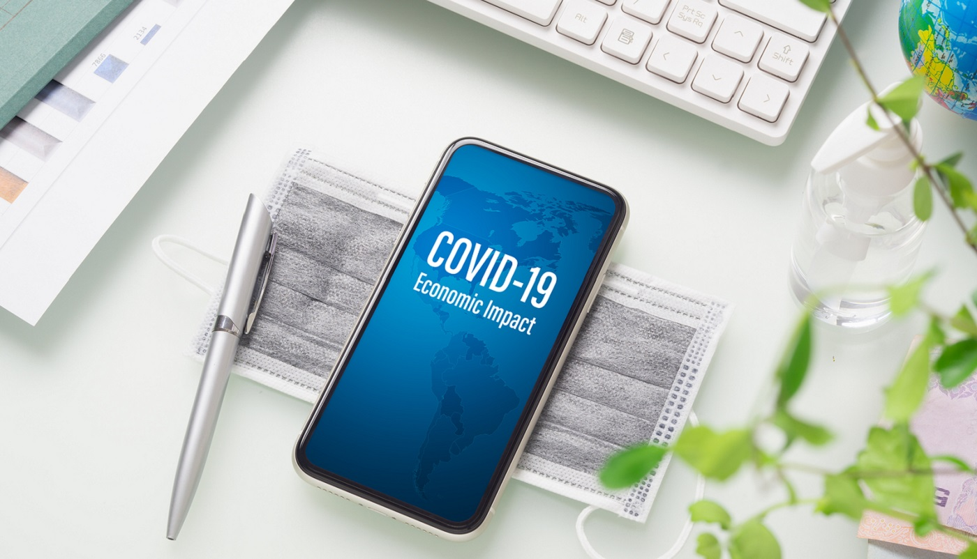 COVID-19 or Corona virus ECONOMIC IMPACT background concept. Mockup mobile phone for Covid 19 business impact with facial masks and Alcohol Mini Hand Sanitizer gel on working office desk table workspace.